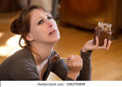 sad looking pretty woman is crying, sitting on the floor and eats lot of chocolate spread with a spoon, trying to forget her problems