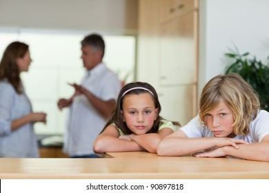 Sad looking siblings with their fighting parents behind them