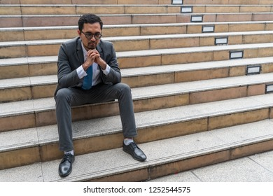 A sad looking young businessman sitting at the staircase looking down with stressed and depressed look gesture