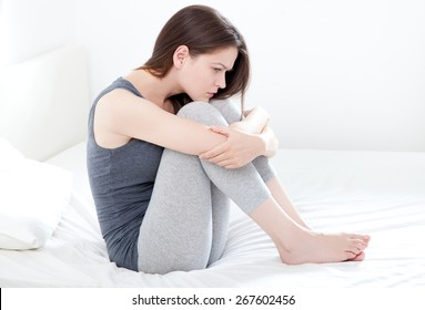 Sad looking young woman sitting on bed, on white background