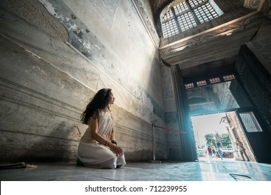 Sad, lost hope, the girl prays in the temple kneeling in the rays of divine light.