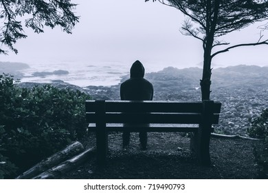 Sad and lovely man sitting on bench overlooking sea on Vancouver Island