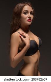 sad luxury girl in black lingerie in dark