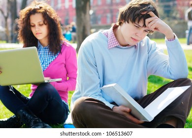 Sad male student with a girl on a background in a park