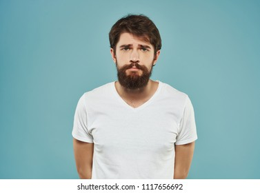 sad man with a beard on a blue background looks at the camera