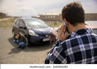 Sad man calling roadside service after car crash