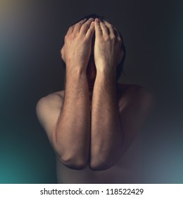Sad man covering face with hands and crying in despair. Chronic depression, grief, sorrow, sadness, melancholy, moaning concept.