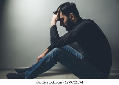 sad man in down on dark background