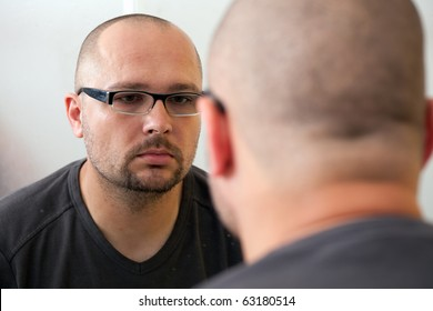 sad man in glasses looks in mirror