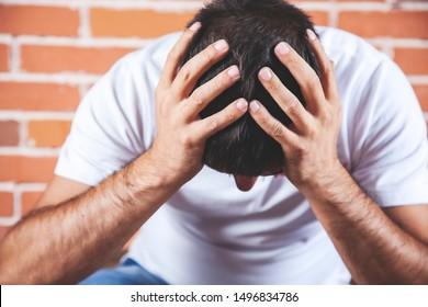 sad man hand in head on brick wall background
