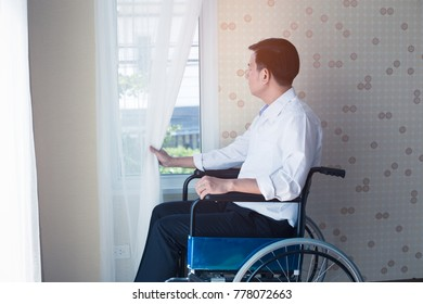 Sad man handicapped sitting on wheelchair in front of window in hospital,He is sad and lonely.