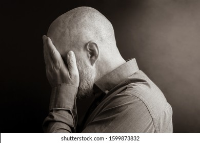 sad man with his hands closed face turned away from the light. despair and depression. shame and guilt. sadness and exile