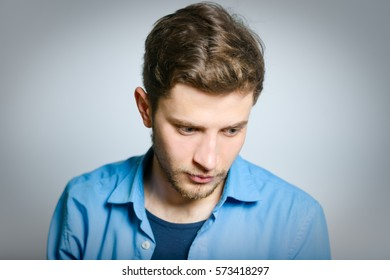 Sad man with his head down, isolated on gray background
