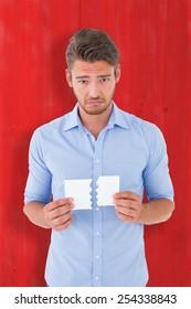 Sad man holding a broken card against red wooden planks