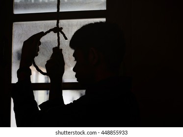 a sad man holding hangman noose in the dark room  against the window while  making decision  to suicide