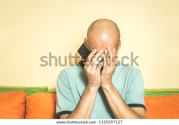 Sad man holding his cell phone in his hands and cry because his girlfriend break up with him over the text message