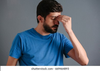 Sad man holding his nose because sinus pain