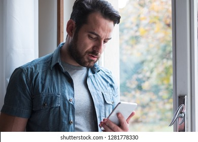 Sad man holding phone alone at home
