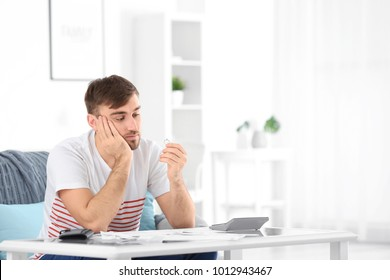 Sad man holding wedding ring at home. Problems in relationship