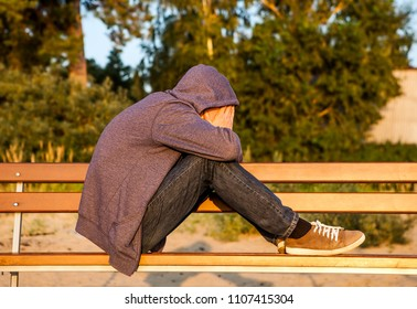 Sad Man in a Hoodie on the Bench outdoor