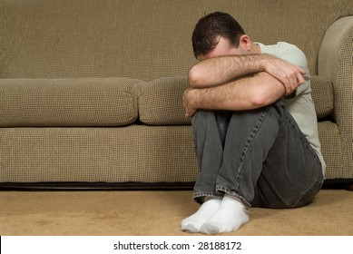 A sad man inside his house, crying into his arm
