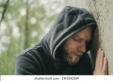 sad man leaning his head against a wall
