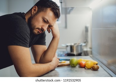 Sad man leaning on the kitchen countertop and looking down