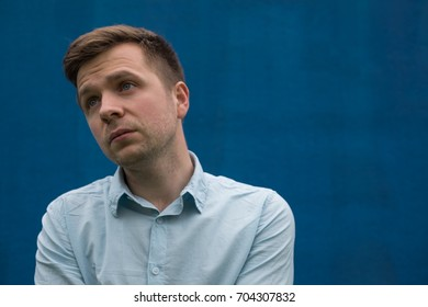 Sad man looking away on blue background. Depression and anxiety disorder concept