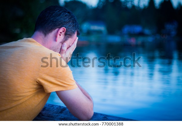 Sad Man Looking Depressed and Hopeless; Face Cupped in Hands, Crying with Back to Camera; Scenic Lake in Background (Blue Tones, Copy Space)