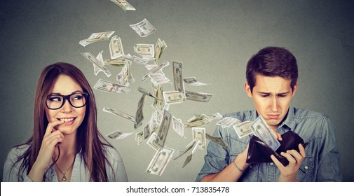 Sad man looking at his wallet with money dollar banknotes flying away towards flirting cute woman