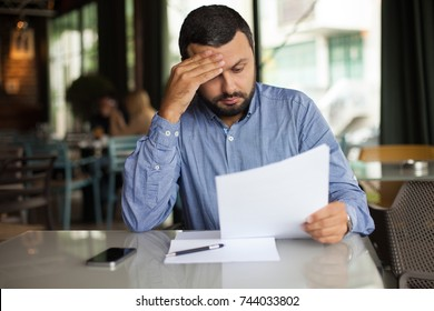 Sad man looking on papers