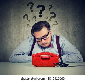Sad man with too many questions waiting for a call