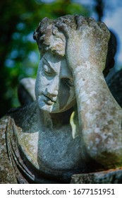 Sad man on tomb as a symbol of depression, pain and sorrow. Fragment of antique stone statue.