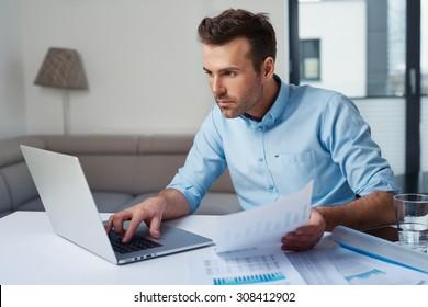 Sad man paying bills on his laptop