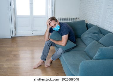 Sad man with protective face mask at home living room couch feeling tired and worried suffering depression amid coronavirus lockdown and social distancing. Mental Health and isolation concept.