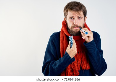 sad man sick with influenza measures the body temperature of a thermometer on a light background, disease, treatment, health, the immune system is weak, feeling unwell