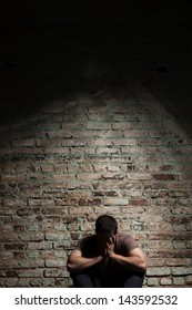 Sad man sitting alone against brick wall.