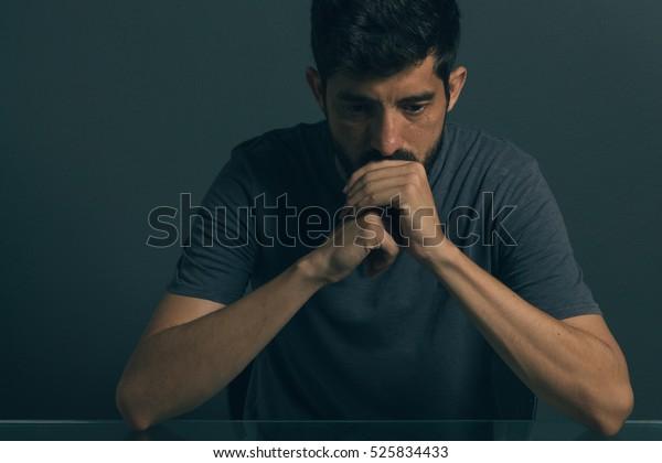 暗い部屋に座っている悲しい男。鬱病と不安障害のコンセプト