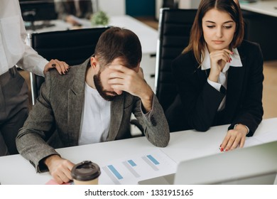 Sad man sitting at the desk in office looking at laptop screen having problem, bad news. Side view of stressed, businessman noticed the error, failed to work, failure in business concept