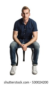 A sad man sitting down on a stool in front of a white background, wearing a blue shirt and jeans with white shoes, looking at camera.