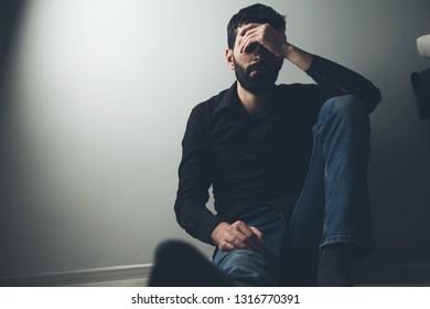 sad man sitting hand in face
