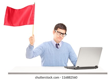 Sad man sitting with laptop and waving a red flag isolated on white background