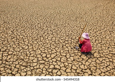 Sad man sitting on dry ground .concept hope and drought