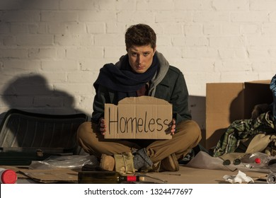 """sad man sitting on rubbish dump and holding cardboard card with """"homeless"""" handwritten text"""