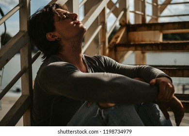 Sad man sitting on the staircase with eyes closed and sunbathing. Beautiful sunny day