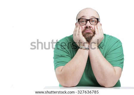 Sad man sitting at the table. Studio photography on a white background.