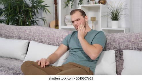 Sad Man Suffer Alone from Tooth Pain or other Dental Problem while Sits on Home Sofa in Apartment Living Room