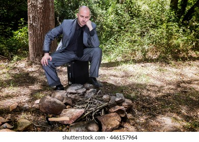 Sad man in a suit in front of a campfire in a forest