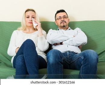 Sad man and unhappy crying woman having conflict at home