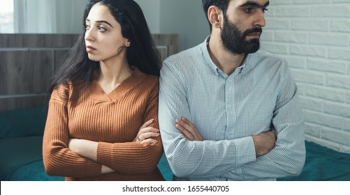 sad man and woman sitting in bed